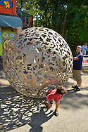 """Huntington, New York, U.S. 24th August 2013. A young boy is stepping out of a rolling metal sculpture """"Sphere of Hope"""" which his father is still in, at the art event """"Off the Walls"""" Block Party, by SPARKBOOM, a Huntington Arts Council project created to help emerging artists, showcase talents, and help its artistic family network. The sculpture is by sculpture Steven Zaluski, and is created from human shapes welded together."""