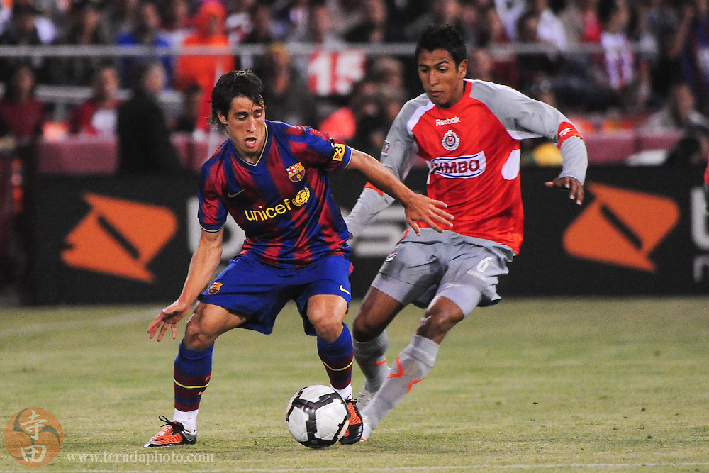 August 8, 2009; San Francisco, CA, USA; FC Barcelona midfielder Jonathan Dos Santos (20, left) controls the ball against Chivas de Guadalajara defender Omar Esparza (6, right) during the second half in the Night of Champions international friendly contest at Candlestick Park. The game ended in a 1-1 tie.