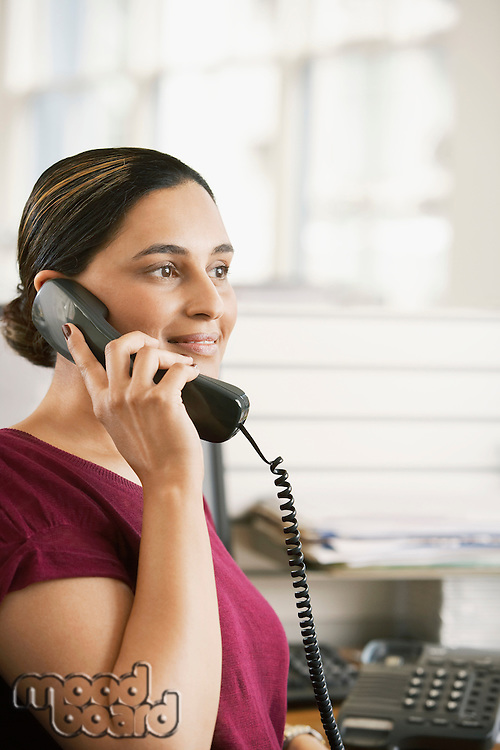 Mid-adult female office worker in cubicle on phone