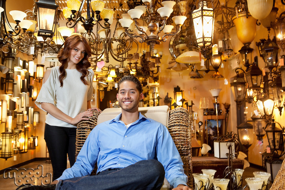 Portrait of handsome young man sitting while woman standing background in lights store