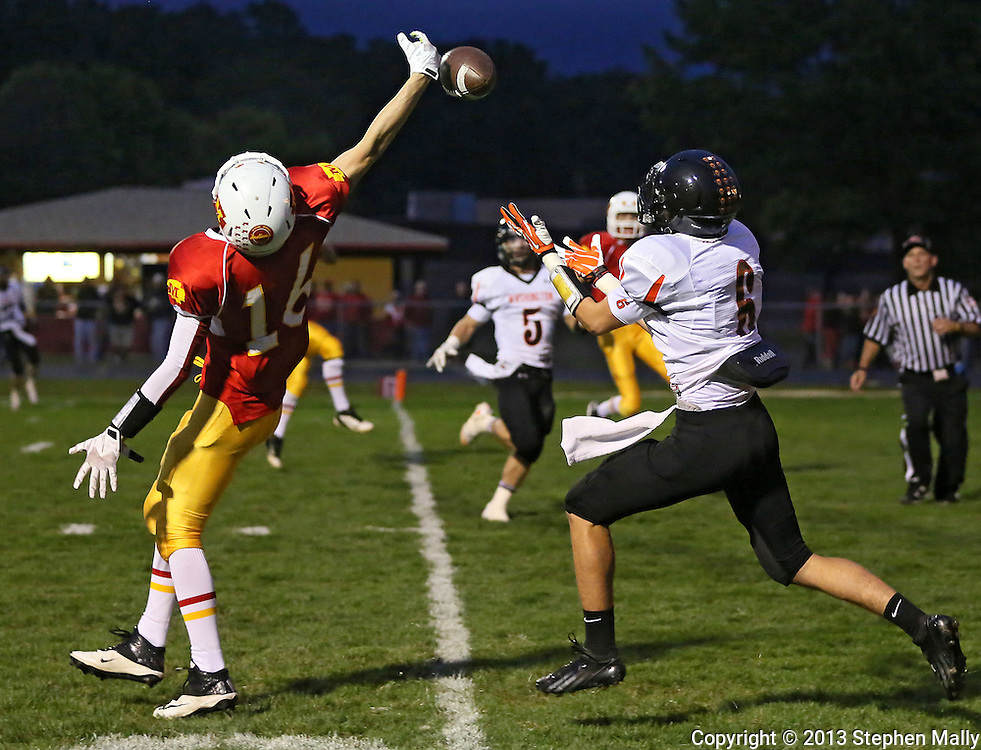Marion's Trevor Hardman (16) breaks up a pass intended for Washington's Jacob Green (6) during their game at Thomas Park Field in Marion on Friday, September 20, 2013.