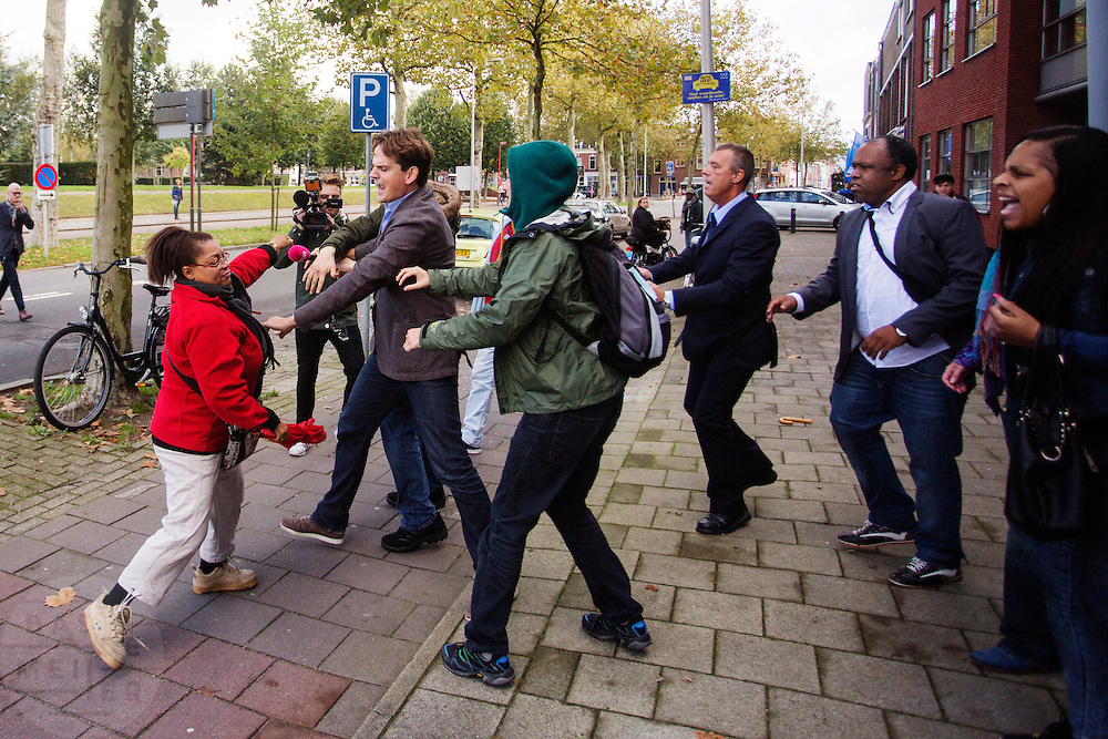 Buiten het collegegebouw ontstaat een opstootje als Pownews enigszins provocerend de tegenstanders van Zwarte Piet willen interviewen. In Utrecht wordt bij het College voor Rechten van de Mens een zitting gehouden over Zwarte Piet. Een Utrechtse moeder vindt Zwarte Piet discriminerend en wil dat een basisschool in Utrecht de hulp van Sinterklaas volledig uit het onderwijsaanbod haalt.<br /> <br /> Outside the college building is a small riot when journalists of PowNews slightly provocative want to interview opponents of Zwarte Piet. In Utrecht at the College of Human Rights a hearing is held about Zwarte Piet (Black Pete). A Utrecht mother takes Zwarte Piet discriminatory and wants a primary school in Utrecht to remove the help of Sinterklaas completely from the curriculum.
