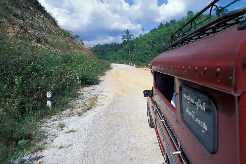 Thailand, Doi Inthanon National Park, Jeep taxi drives along dirt road through jungle hills south of Chiang Mai