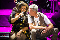 © Licensed to London News Pictures . 01/07/2017 . Manchester , UK . Rowetta Idah and Bez (Mark Berry). Hacienda Classical play at the Castlefield Bowl as part of Sounds of the City , during the Manchester International Festival . A collaboration between DJs Mike Pickering and Graeme Park and the Manchester Camerata orchestra , Hacienda Classical reworks music by bands including the Happy Mondays and New Order and features Manchester musicians including Rowetta and Peter Hook . Photo credit : Joel Goodman/LNP