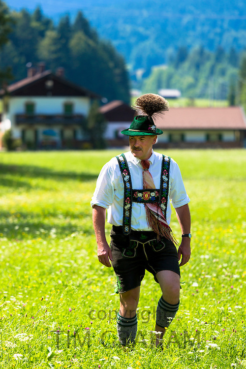 Man in costume strolls through flower meadow during traditional beer festival in the village of Klais in Bavaria, Germany