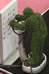 © Licensed to London News Pictures.  16/03/2012. LONDON, UK. A man dressed as a hedge tries out an exercise machine at the Ideal Home Show exhibition in Earls Court, London. The show begins today and runs from the rest of March. Photo credit :  Cliff Hide/LNP