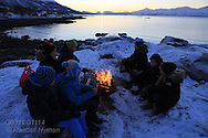 Kids gather around fire on rocky shore at Telegrafbukta at the south end of Tromsoya island on January 21st watching return of the sun after its two-month absence ; Tromso, Norway.
