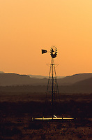 windmill in the desert to pump water out of the ground at sunset in the heat of the evening