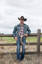 hot cowboy with a lasso against a  wooden fence