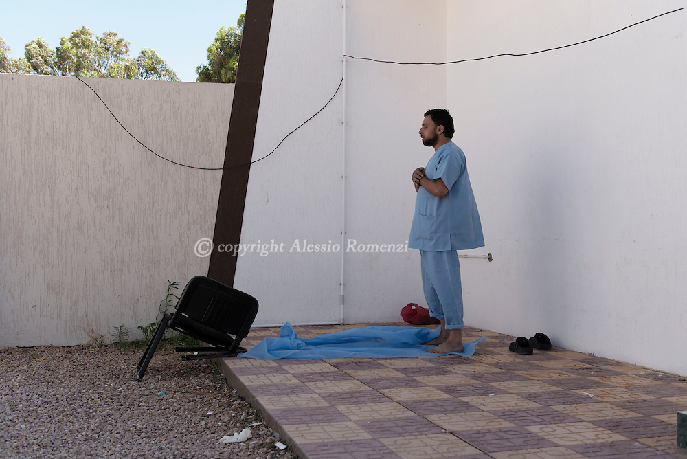 Libya: A Libyan doctor prays in front of a makeshift hospital in Sirte. Alessio Romenzi
