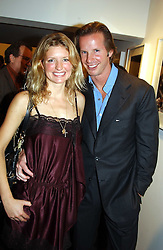 CHRISTOPHER GETTY and LAINEY SHERIDAN-YOUNG at an exhibition of photographs by Matthew Mellon entitled Famous Feet - featuring well known people wearing shoes from Harrys of London, held at Hamiltons Gallery, Carlos Place, London on 22nd November 2004.<br />