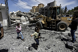 May 5, 2019 - Gaza City, The Gaza Strip, Palestine - Palestinians are seen inspecting the remains of a building which was destroyed during the Israeli air strikes in Gaza City..According to media reports, more than 250 rockets have been fired into Israel by billions, and Israel has responded back with air strikes and tank fire on Palestinian territory. (Credit Image: © Mahmoud Issa/SOPA Images via ZUMA Wire)