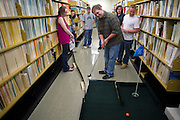 Matt Crabtree (Center), a Hocking College student, putts during the Alden Open mini golf event in Alden Library on Friday evening, April 15, 2011.
