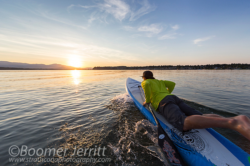 A stand up paddleboarder launches his board into the evening waters of Comox Bay.  The Comox Valley, Vancouver Island, British Columbia, Canada