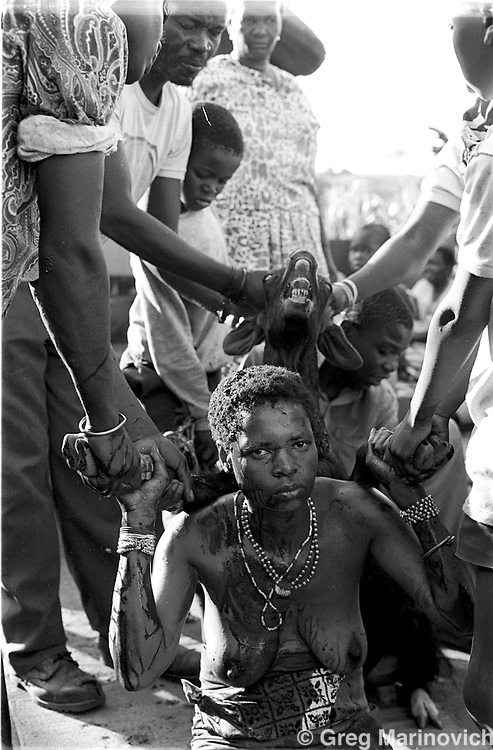 A sacrificial goat is killed over Sowetan Cookie Kashane at her initiation as Ndau medium / diviner at Dolly Village, Venda, South Africa Feb 4, 1991. (Greg Marinovich)