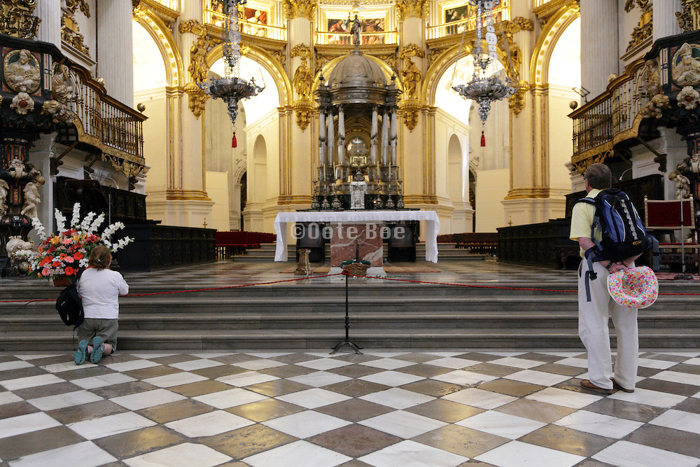 woman kneeling by main altar inside Cathedral Granada Spain with a male tourist on the side
