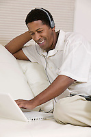Man sitting on sofa using laptop with headphones