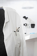 Scientists white coat in laboratory with microscope in background