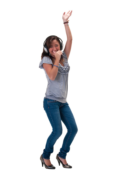 Young latin girl listening to music and dancing very happy.