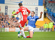 Christian Burgess tackles Adam Buxton during the Sky Bet League 2 match between Portsmouth and Accrington Stanley at Fratton Park, Portsmouth, England on 5 September 2015. Photo by Adam Rivers.