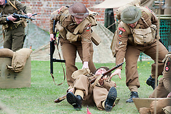 Reenactors of the NWW2A Portraying members of the Duke of Wellingtons Regiment pull a wounded comrade to safety during a battle reenactment at Fort Paull on Sunday ..5 May 2013.Image © Paul David Drabble