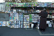 Paris, France, December, 2005-A woman browses at a Bookiniste stall along the Seine.