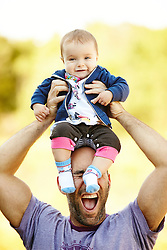 Farther Holding Baby Daughter above his Head