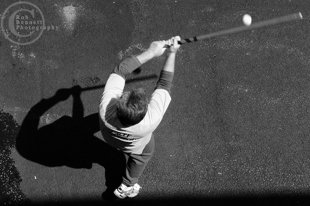 "Jack ""Late Lightning"" Dammann,  71 and a college professor from Queens, bats during a game of stickball as seen from a second story school window..---.The Ethical Stickball League has been operating since 1970, meeting every Sunday in the parking lot behind Hastings High School from 10:30AM to 1PM.  The players are men now mostly in their 70s - carrying nicknames like ""The Wise One"", ""Hit Man"" and ""Plays Hurt"" - who have an affiliation with the school, either as former teachers, students or neighbors. As their slogan suggests, all it takes for a few hours of ""Aestas Aeterna"" (Eternal Summer) is an outside temperature above 45 degrees and 8 willing souls...CREDIT: Rob Bennett for The NY Times"