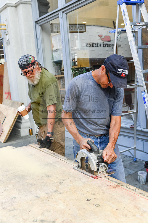 Charleston, South Carolina, USA. 03 September 2019. Workers cut plywood to cover the windows of a shop on historic King Street in preparation for Hurricane Dorian September 3, 2019 in Charleston, South Carolina. The slow moving monster storm devastated the Bahamas and is expected to reach Charleston as a Category 2 by Thursday morning.
