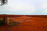landscape photography: rural landscape with open white gate leading into open ploughed field of saturated red dirt