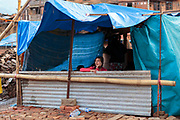 Beneath hastily assembled tarpaulins, a woman takes shelter after her family home was destroyed by the 2015 Nepal earthquake.