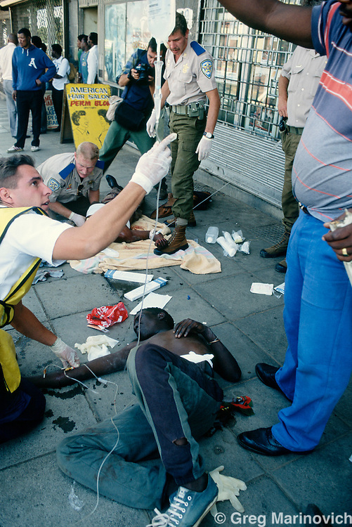 Johannesburg, South Africa, 1994. Medics use IV to treat a wounded Zulu after African National Congress guards opened fire on Inkatha Freedom Party marchers when they approached the ANC headquarters of Shellhouse, Johannesburg 1994. Many IFP supporters killed and wounded. Others were shot from the rooftops by persons unknown at the nearby Library Gardens. Johannesburg, South Africa