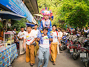 05 APRIL 2013 - CHIANG MAI, THAILAND: A boy is carried through the grounds of Wat Pa Pao during the Poi Sang Long festival. The Poi Sang Long Festival at Wat Pa Pao in Chiang Mai, Thailand, is an annual festival that marks the ordination of boys in the temple as novice monks. Hundreds of people attend the festival, which is marked by the boys wearing garish makeup and being carried through the temple grounds on the shoulders of older men while musicians play drums and cymbals.     PHOTO BY JACK KURTZ