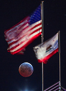 The moon knows as Blood Moon is seen behind the U.S. and California State flags during a total lunar eclipse on April 4, 2015 in Los Angeles, California, the United States. The total eclipse last 4 minutes, 43 seconds, making it the shortest lunar eclipse for the rest of the 21st Century.