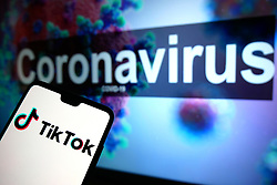 The TikTok logo seen displayed on a mobile phone with an illustrative model of the Coronavirus displayed on a monitor in the background. Photo credit should read: James Warwick/EMPICS Entertainment