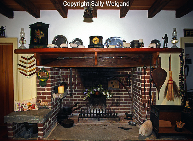 walk-in fireplace, cooking utensils, wood beam mantle, stone hearth