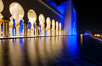 UNITED ARAB EMIRATES, ABU DHABI - CIRCA JANUARY 2017:  Pool, arches and columns of the Sheikh Zayed Mosque at night.