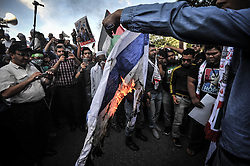 Image licensed to i-Images Picture Agency. 18/07/2014. Kuala Lumpur,Malaysia.Demonstrators burn an Israeli flag as they protest against Israel's military action in Gaza during a demonstration in front of the US embassy in Kuala Lumpur on July 18, 2014.Picture by Mohd Firdaus / i-Images