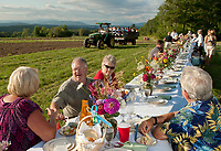 "Diane and John Goodhue along with Dave and Katie Ewing enjoy their view as the remaining diners arrive by tractor for the Beans and Greens ""Farm to Table Dinner in the Field""  Wednesday evening.  (Karen Bobotas/for the Laconia Daily Sun)"