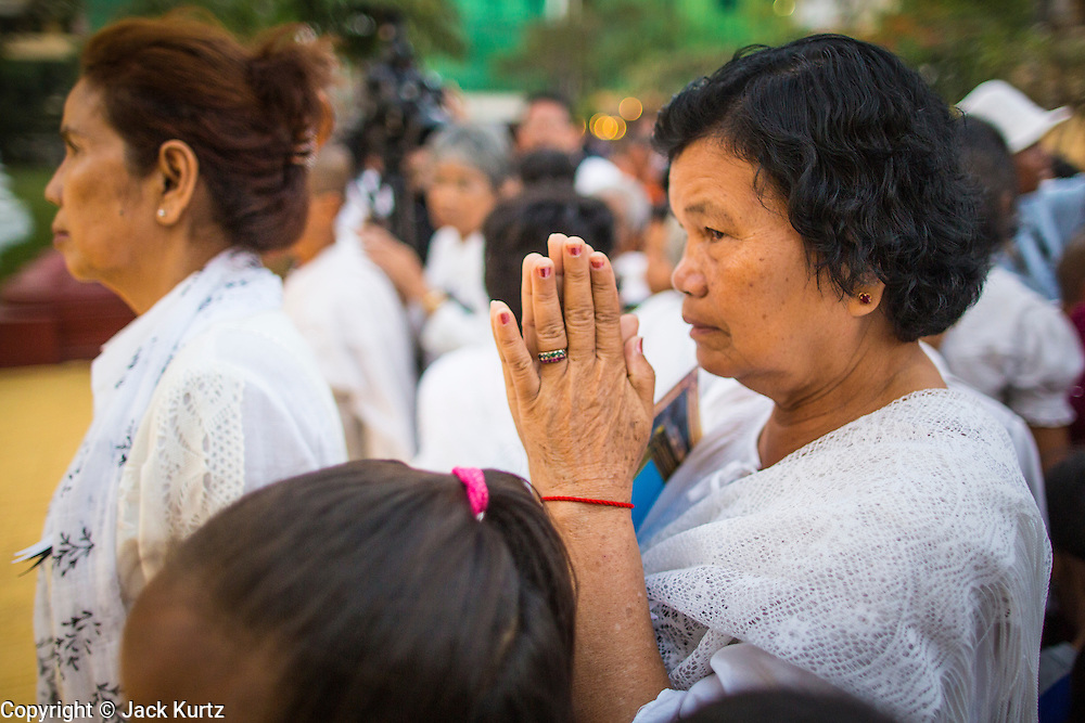 "30 JANUARY 2013 - PHNOM PENH, CAMBODIA:    A Cambodian woman wearing white mourning clothing prays for late Cambodian King Norodom Sihanouk in Phnom Penh. Sihanouk (31 October 1922 - 15 October 2012) was the King of Cambodia from 1941 to 1955 and again from 1993 to 2004. He was the effective ruler of Cambodia from 1953 to 1970. After his second abdication in 2004, he was given the honorific of ""The King-Father of Cambodia."" Sihanouk held so many positions since 1941 that the Guinness Book of World Records identifies him as the politician who has served the world's greatest variety of political offices. These included two terms as king, two as sovereign prince, one as president, two as prime minister, as well as numerous positions as leader of various governments-in-exile. He served as puppet head of state for the Khmer Rouge government in 1975-1976. Most of these positions were only honorific, including the last position as constitutional king of Cambodia. Sihanouk's actual period of effective rule over Cambodia was from 9 November 1953, when Cambodia gained its independence from France, until 18 March 1970, when General Lon Nol and the National Assembly deposed him. Upon his final abdication, the Cambodian throne council appointed Norodom Sihamoni, one of Sihanouk's sons, as the new king. Sihanouk died in Beijing, China, where he was receiving medical care, on Oct. 15, 2012. His cremation is scheduled to take place on Feb. 4, 2013. Over a million people are expected to attend the service.        PHOTO BY JACK KURTZ"