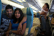 Honeymoon couple on their return home after a holiday in the Maldives return home in economy class, happy.