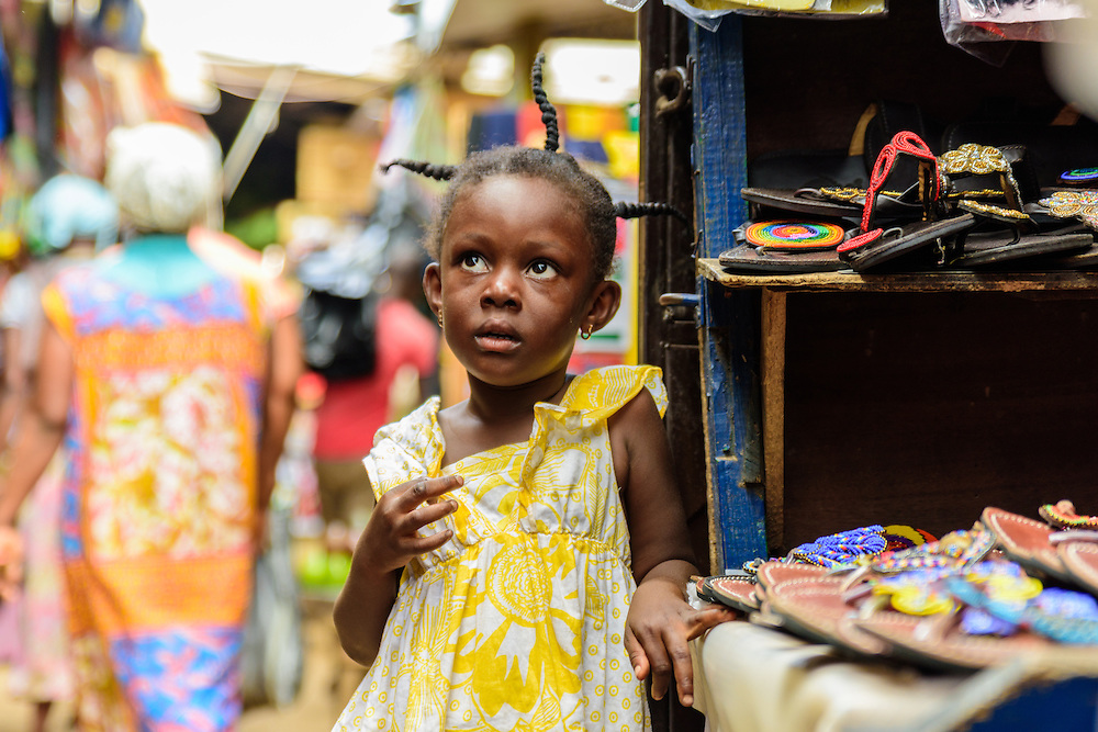 Little girl with rasta's and a yellow dress on the market, Tema, Ghana.