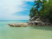 """A boy climbs on the rocks.  Image from the area known as """"The Cove,"""" Pictured Rocks National Lakeshore, Michigan, USA."""