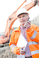 Supervisor holding clipboard while using walkie-talkie at construction site