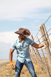 cowboy on a rustic ranch by a fence