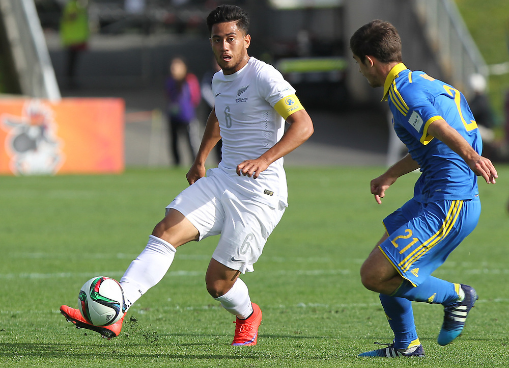 Bill Tuiloma of New Zealand passes the ball past Ihor Kharatin of Ukraine in the opening game of the FIFA u20 World Cup at QBE Stadium, Auckland, New Zealand, Saturday, May 30, 2015. Credit:SNPA / Ben Campbell