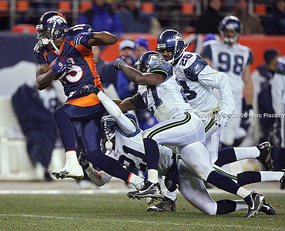 In the fourth quarter, the Denver Broncos Brandon Marshall (#15, WR) breaks the tackles of the Seattle Seahawks Kelly Jennings (#21, CB), Jordan Babineaux (#27, SS) and Michael Boulware (#28, SS) on his way to a 71 yard touchdown reception at Invesco Field at Mile High on Sunday December 3, 2006. The game marked the first career start for rookie quarterback Jay Cutler. The Broncos lost the game 23-20, committing five turnovers in the loss. The touchdown tied the game at 20-20 at this point..(MARC PISCOTTY/ © 2006)