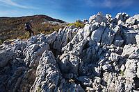 Hiker (Dan Dinu) on a rocky limestone ridge in Mehedinti Plateau Geopark. Geoparcul Platoul Mehedinți, Romania.