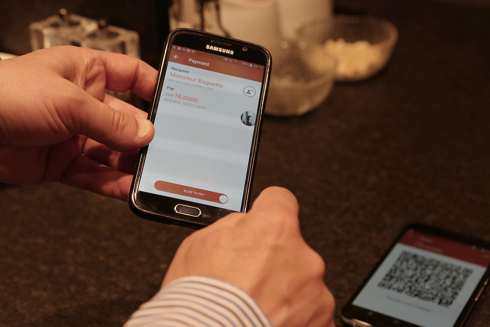 Vitus Ammann, CMO of Monetas, showing how he uses the Monetas app to pay in a Zug Café, Monsieur Baguette, in Zug Kanton, Switzerland