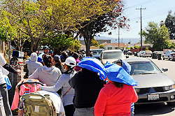 Hebbron residents use food distribution bags for shade as they wait in line at St. Clare's Corner, established in Salinas by the Franciscan Workers of Junipero Serra in 1982. Supplied by the Food Bank of Monterey County, basic foodstuffs like rice and beans supplement family diets from October to May, the winter months when unemployment is highest.